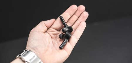 A hand holding Blank wireless earphones on black background