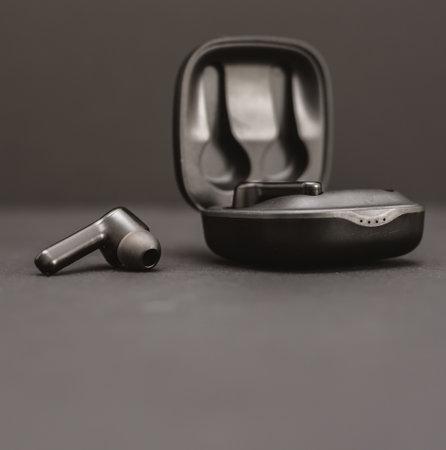 Blank wireless earphones on black background
