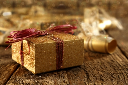 gold gift box on rustic plank table photo