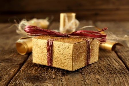 gold present box on rustic table photo
