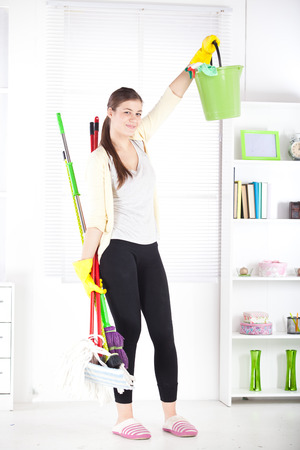 Young woman smiling while cleaning and doing housework