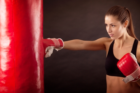 Female athlete with a punching bag photo