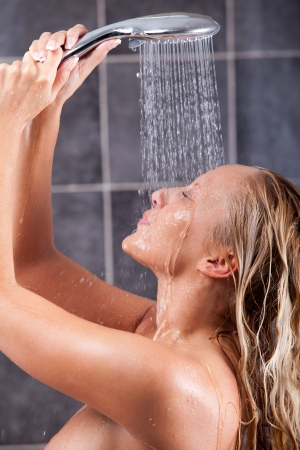 Young woman taking a shower and enjoying it