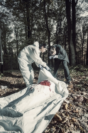 CSI team of experts inspecting a dead body photo