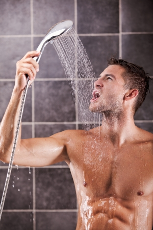 Handsome man taking a shower and enjoying it photo