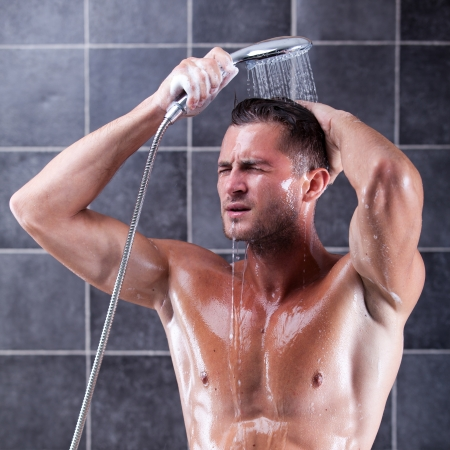 Handsome man taking a shower and enjoying it Stock Photo