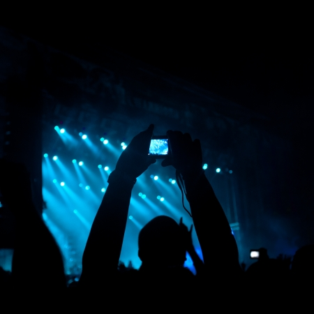 silhouettes of people on a rock concert raising hands, stage light in background.  NOTE - Some noise and artefacts visible due the use of high ISO because of difficult lighting conditions  photo