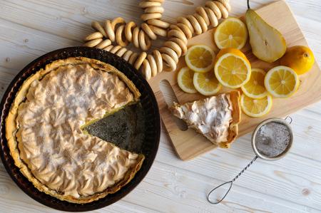 lemon wedge: Fresh homemade lemon tart for Breakfast with a slice of lemon for a simple light wooden background.