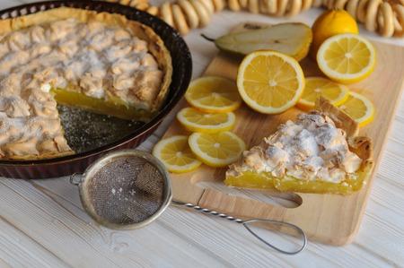 Fresh homemade lemon tart for Breakfast with a slice of lemon for a simple light wooden background.