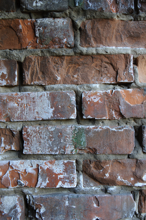 Background of old vintage dirty brick wall with peeling plaster, texture. Stock Photo