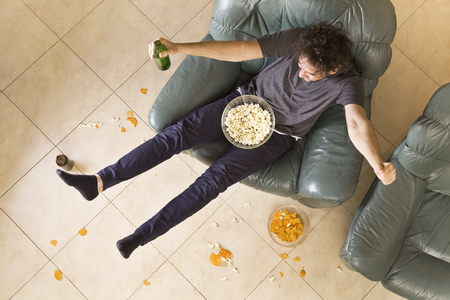 Top view of excited young man with beer and chips on the couch