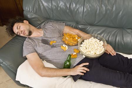 Un homme endormi sur un canapé dans un désordre de malbouffe