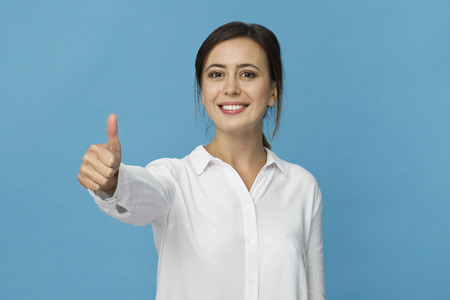 Smiling positive female with attractive look, wearing white T-shirt, posing against blue blank wall with OK gesture