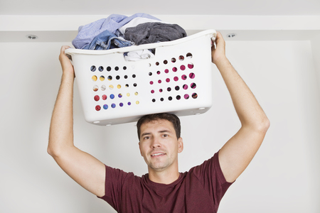 Portrait of smiling husband holding basket full of clothes on his head against white wall
