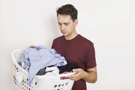 Frustrated young man holding basket full of clothes. Laundry time Imagens