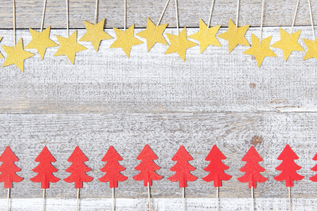Home made decorations, golden stars and red Christmas trees on white wooden background. Retro style