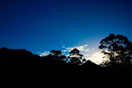 On a hike in cradle mountain national park the beautiful trees and hillside made a beautiful silhouette at sunset photo