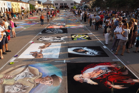 Curtatone, italy 16082016: pavement street artist finishing painting over the asphalt in Madonnari word competition of chalk paintings, from the Sanctuary of the Blessed Virgin of Graces.