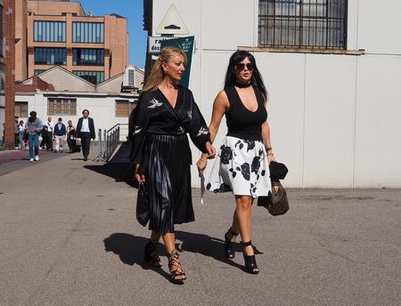 MILAN - SEPTEMBER 21: Two fashionable women walking after LES COPAINS fashion show, during Milan Fashion Week spring  summer 2018 on September 21, 2017 in Milan