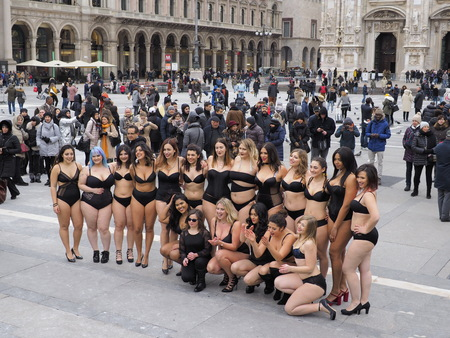 MILAN - FEBRUARY 25, 2018: Craziest women in swimsuit and hight heels in Duomo square celebrate hen party in frost day. Milan, Italy, 25 February 2018
