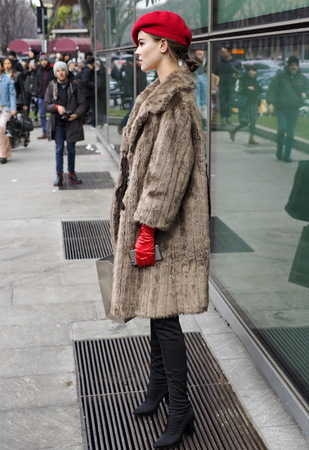 MILAN - FEBRUARY 25, 2018: Fashionable model posing for photographers in the street before the ARMANI fashion show, during Milan Fashion Week. Fall / winter 2018/19 in Milan, Italy. Editorial