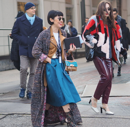 MILAN - FEBRUARY 24, 2018: Fashionable women walking in the street for photographers before CIVIDINI fashion show, during Milan Fashion Week Woman fall  winter 201819 in Milan, Italy.