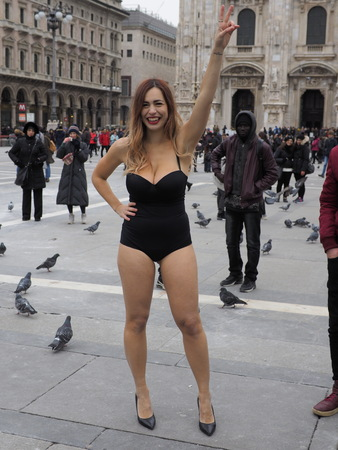 MILAN - FEBRUARY 25, 2018: Crazy woman in swimsuit and hight heels in cathedral square celebrates friend hen party in frost day. Milan, Italy, 25 February 2018.