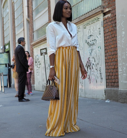 MILAN, ITALY -JUNE 18, 2018: Fashionable woman posing for photographers in the street before FENDI fashion show, during Milan Fashion Week Men and women spring collections.