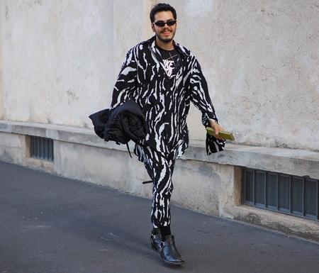 MILAN, Italy- SEPTEMBER 20: Man walking for photographers in the street before the PRADA fashion show, during Milan Fashion Week fall winter 2019 on September 20, 2018. Editorial