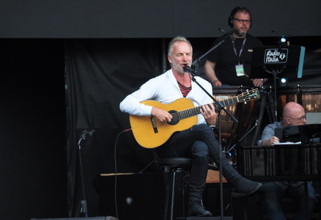 MILAN, Italy: May 26, 2019: Sting, famous guitarist and singer, during orchestra rehearsals and acoustic test in Duomo square Milan for Radio Italia. Imagens - 124156518