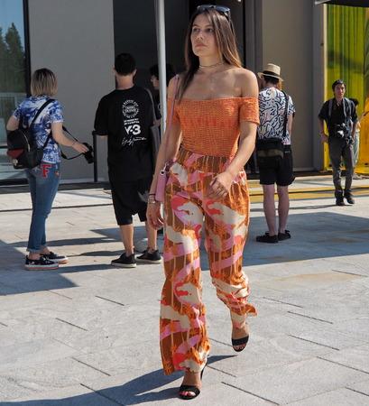MILAN, ITALY -JUNE 16, 2018: Fashionable woman walking in the street after Neil Barrett fashion show, during Milan Fashion Week.