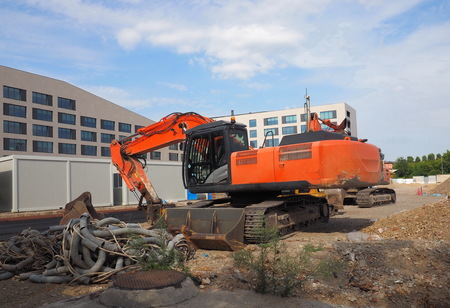 Milan, Italy: 17 August 2019: Escavator in a new area of Milan buildind behind Olivetti square