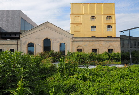 Milan, ITALY 17 August 2019 - Prada museum foundation - golden yellow warm building in the new square Adriano Olivetti in the south of town Editorial
