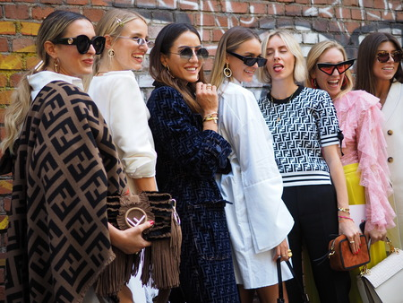 MILAN, Italy- SEPTEMBER 20: Fashion bloggers posing for photographers in the street after FENDI fashion show, during Milan Fashion Week spring  summer 2019 on September 20, 2018.
