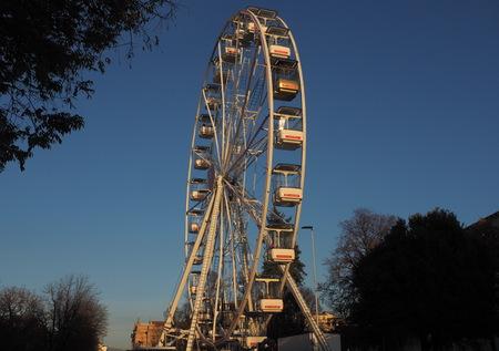 Bergamo, Italy: November 25, 2019: Ferris Wheel against the Blue Sky in the city center of Bergamo Sunny Day. Rotating Ferris wheel with cabins.
