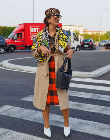 MILAN, Italy- SEPTEMBER 20: A fashionable woman posing for photographers in the street before PRADA fashion show, during Milan Fashion Week fall winter 2019 on September 20, 2018.