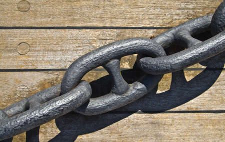 iron chain for boats anchor on a wooden plan. Stock Photo