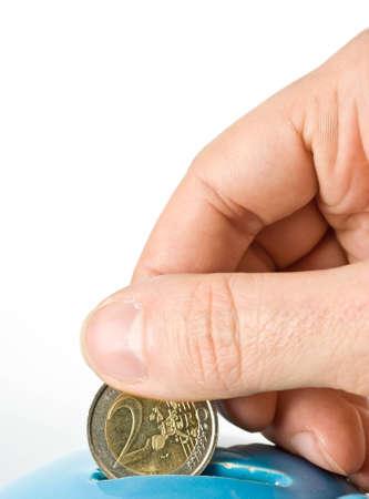 An hand puts a money into a blue moneybox