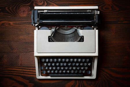 Old typewriter on wooden table with a blank bloc notes