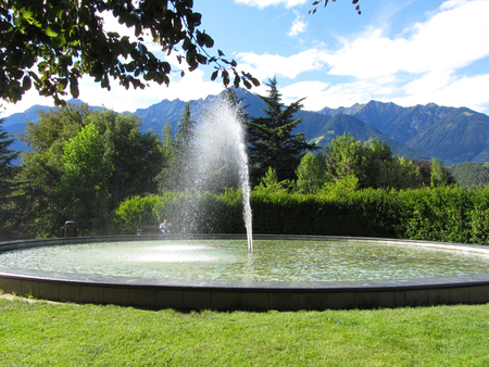 Water fountain with mountain background in a bright sunny day photo