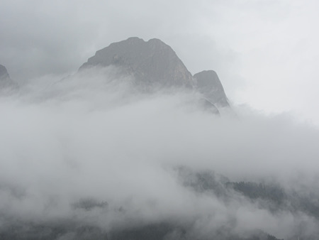 shrouded: Panoramic view of the Dolomites shrouded by clouds near Castelrotto, South Tyrol - Italy