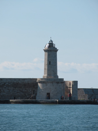 lighthouse keeper: Harbor lighthouse and its keeper in a sunny day during summer. Livorno, Italy