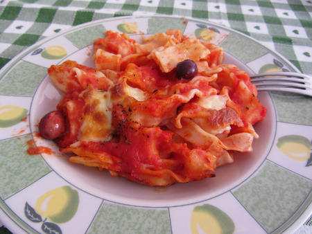 durum: Plate of home made italian baked pasta on the table. The ingredients are italian pasta made with durum wheat tomato sauce mozzarella basil origan olive oil olives