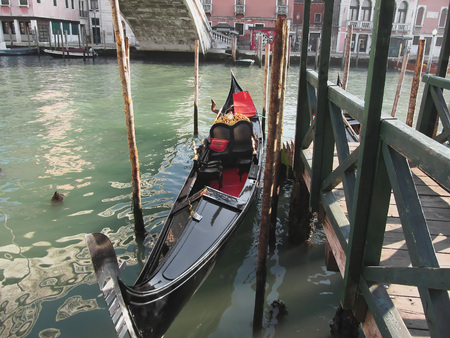 venice canal: Gondola moored by quay on Venice canal, Italy Stock Photo
