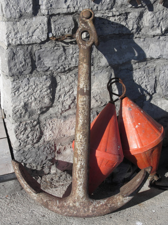 demarcation: A rusty anchor and two orange conical buoys at the marina