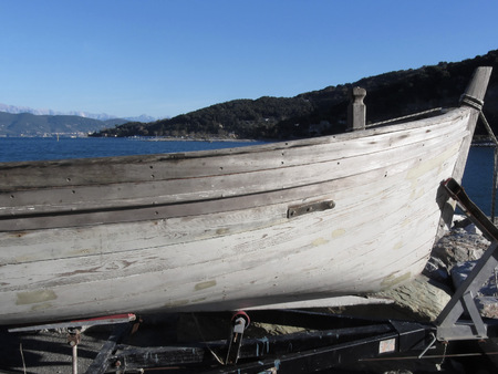 repaint: Hull of wooden fishing boat under repair in dry dock in Portovenere, Province of La Spezia, Italy