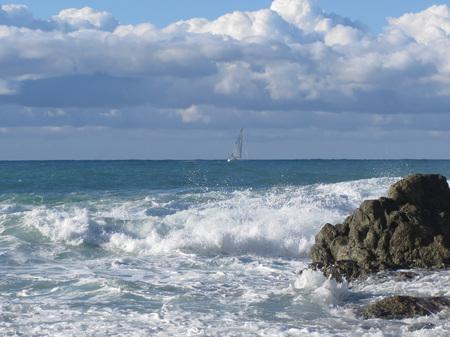 wavely: Stormy sea and sailboat along Tuscany coastline in Livorno, Italy Stock Photo
