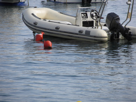 outboard: Single inflatable dinghy with outboard motor lies at anchor in a harbor . Tuscany, Italy