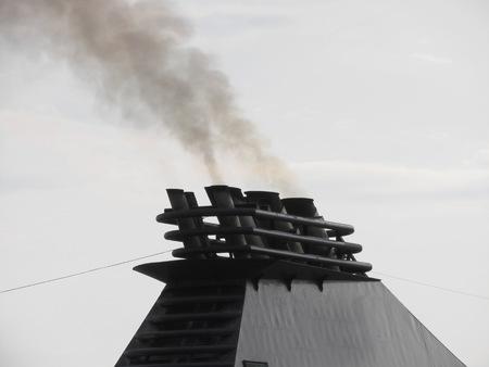 Ships funnel emitting black smoke in the sky