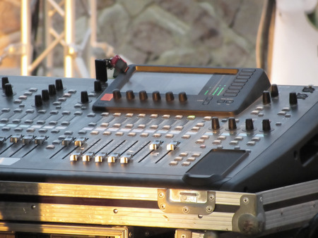 adjuster: Professional audio mixing console with faders and adjusting knobs for party outdoor at sunset